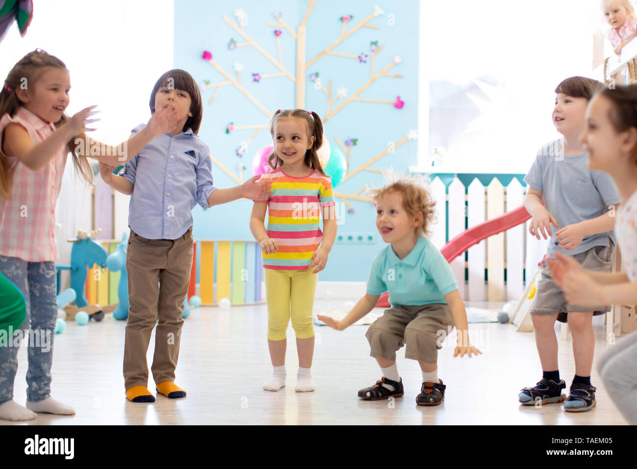 Group of happy children jumping indoor. Kids play together - Stock Image