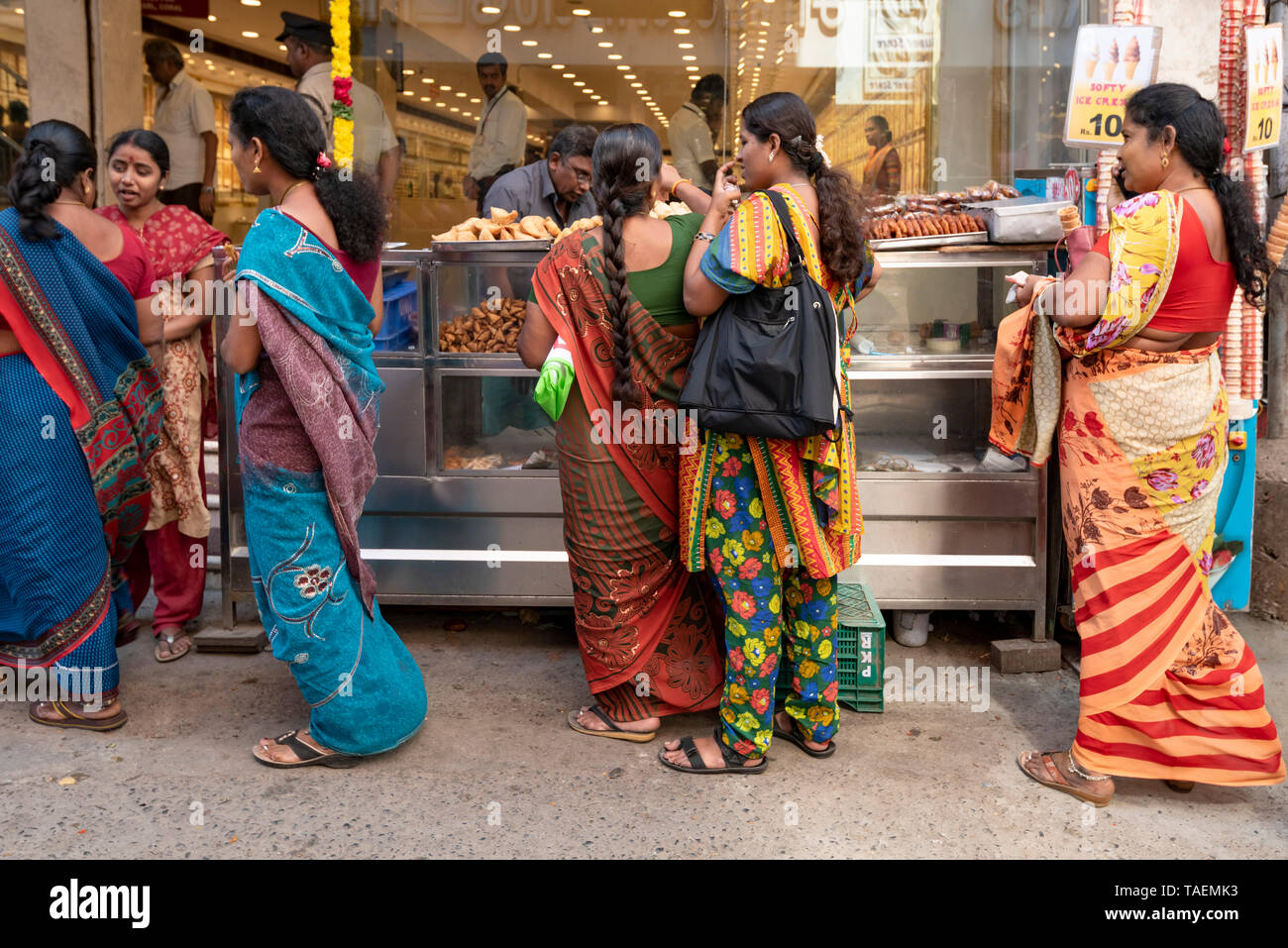 Horizontal view of ladies queueing at a streetfood stall in India. Stock Photo