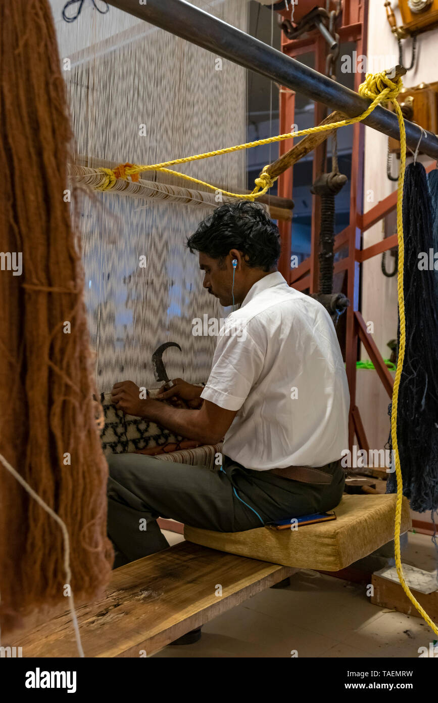 Vertical view of a man listening to his iphone whilst using an old fashioned vertical loom in India. - Stock Image