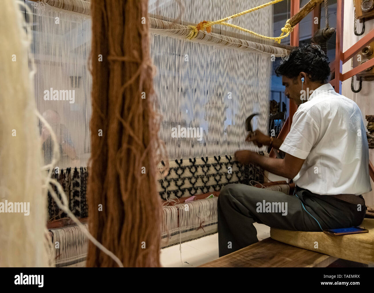 Horizontal view of a man listening to his iphone whilst using an old fashioned vertical loom in India. - Stock Image