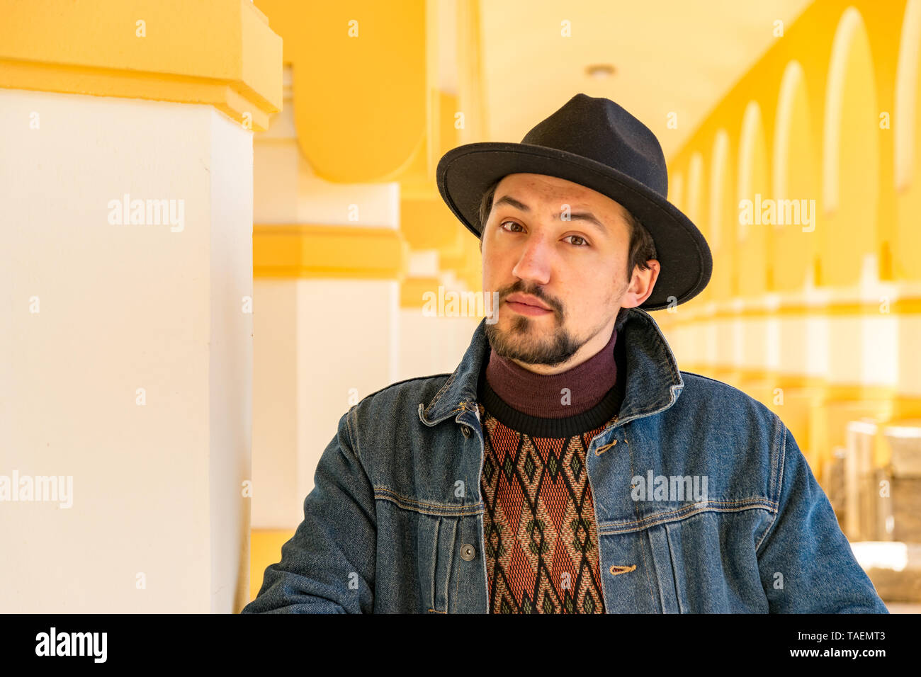 Portrait of a stylish handsome young man with a scarf outdoors.  A serious man wearing a hat and a jaket looking confident at the camera. Stock Photo