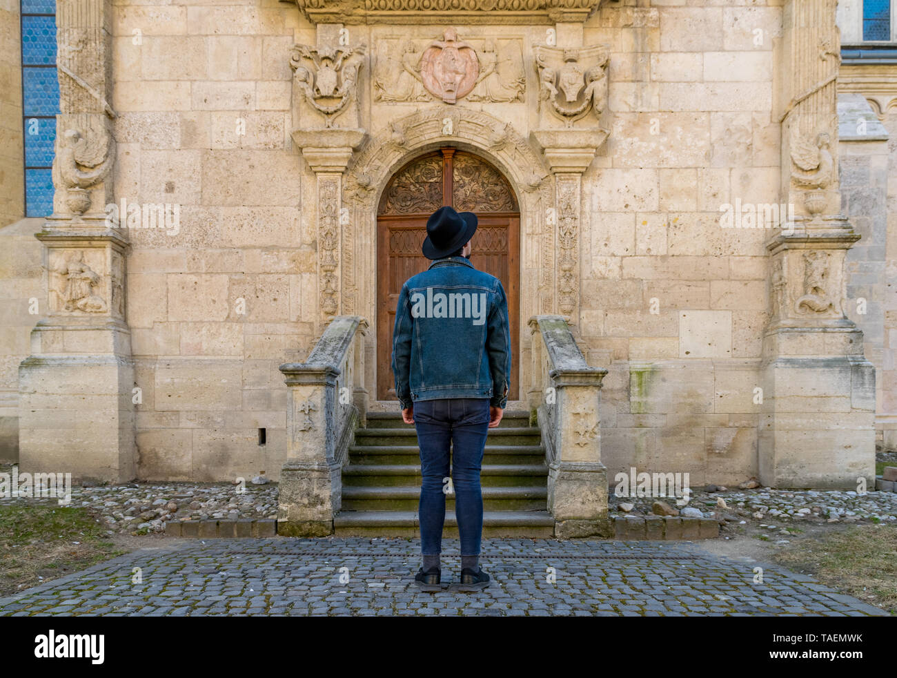 A tourist young man standing against a beautiful old medieval chatedral door. A man  in front of a an old architecture church entrance door in Alba Iu Stock Photo