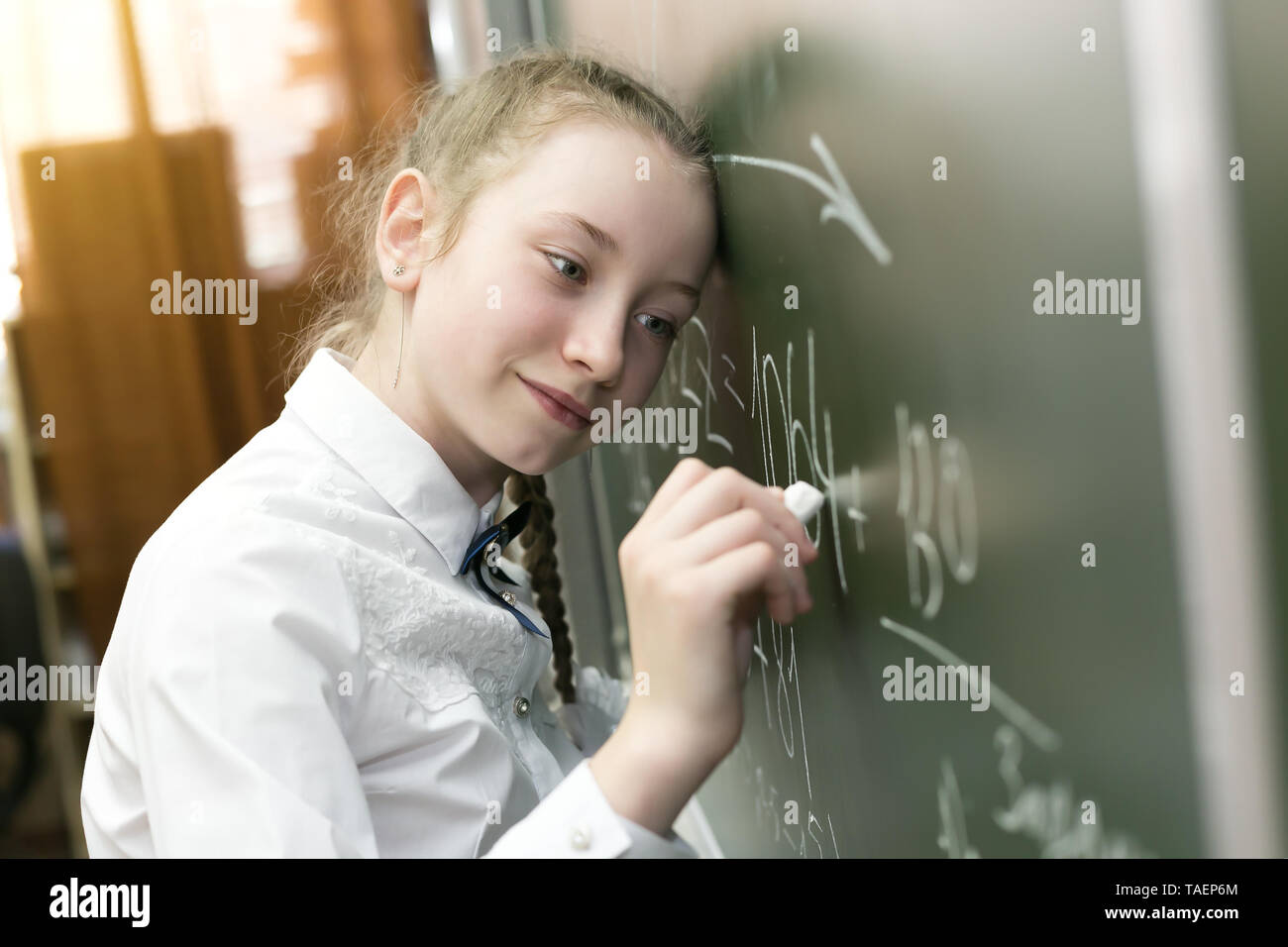 A girl schoolgirl is tired tends to sleep with fatigue, put her head on the school board. - Stock Image