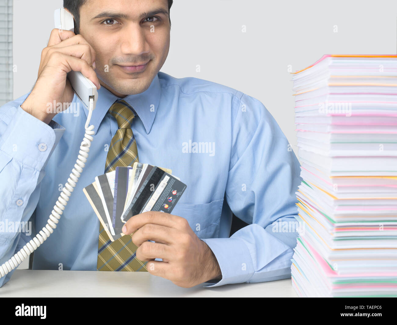 CORPORATE EXECUTIVE HOLDING MULTIPLE CREDIT CARDS WITH A HEAP OF PAPERS ON HIS DESK Stock Photo