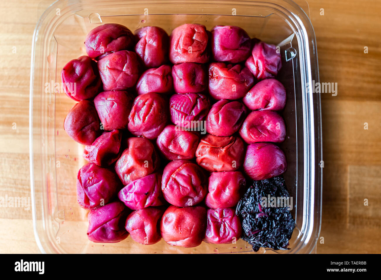 Traditional japanese storebought red umeboshi pickles made with ume plum flat top closeup on wooden table with pink shiso leaf - Stock Image