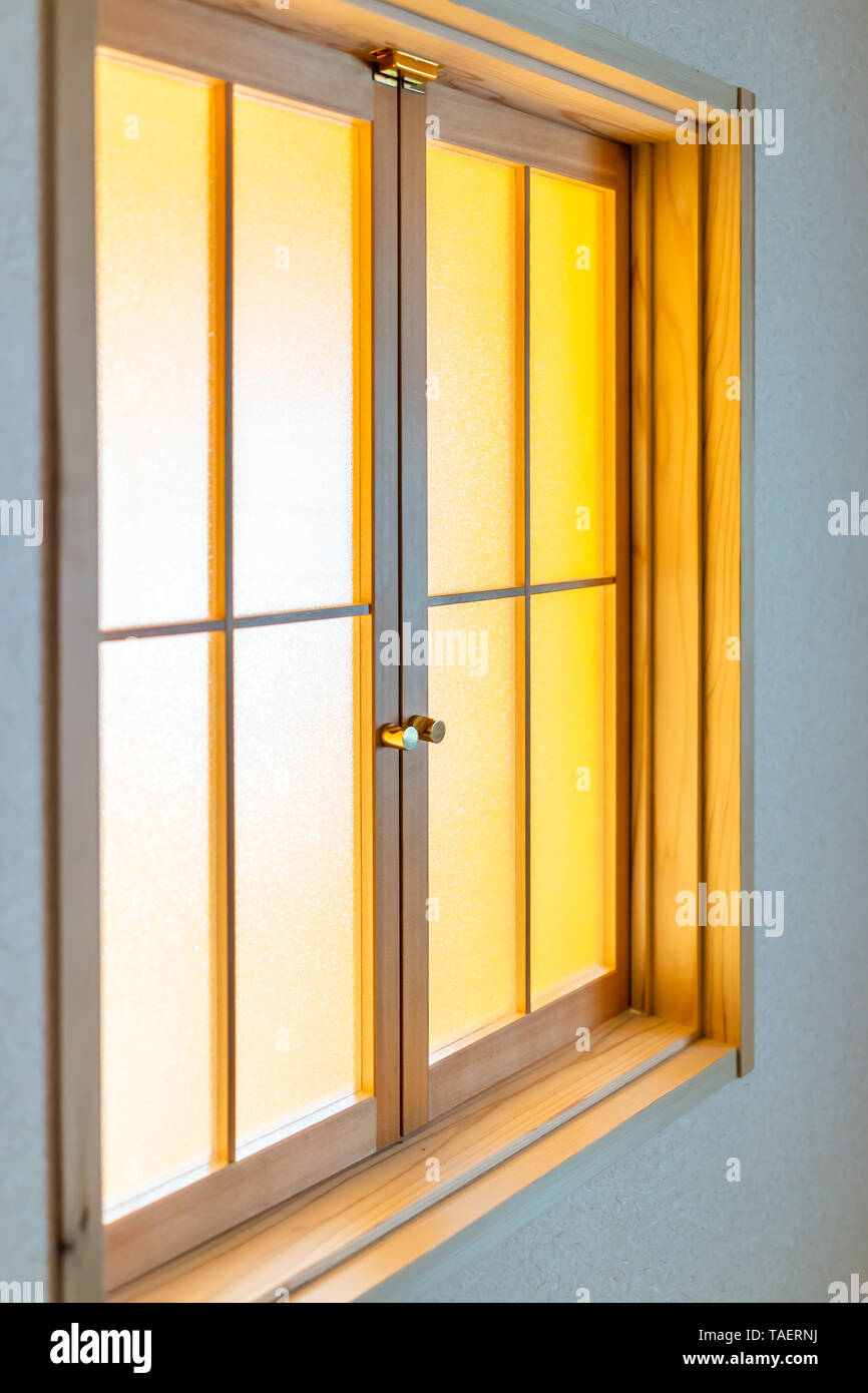 Traditional japanese house or ryokan with closeup of closed window door with transparent glass and yellow light - Stock Image