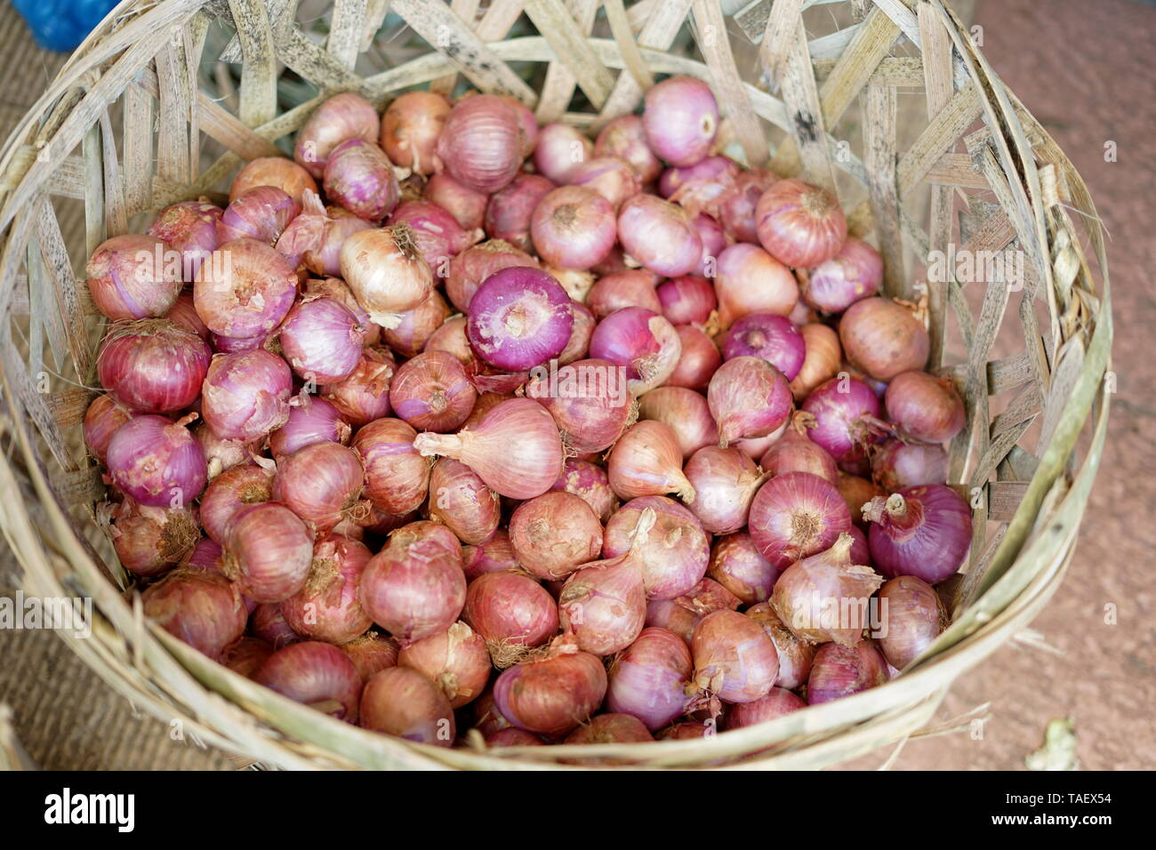Fresh Red Onions in the Basket at traditional vegetable market - Stock Image
