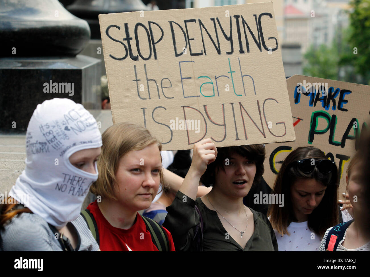 A demonstrator seen holding a placard that says stop denying the earth is dying during the climate strike. Climate strike as part of a global day of student protest, the Fridays for Future movement aiming to spark the world leaders into action on climate change near the Ukrainian Cabinet of Ministers in Kiev, Ukraine. Organizers expect more than one million young people over the world to join protest against global warming. Stock Photo