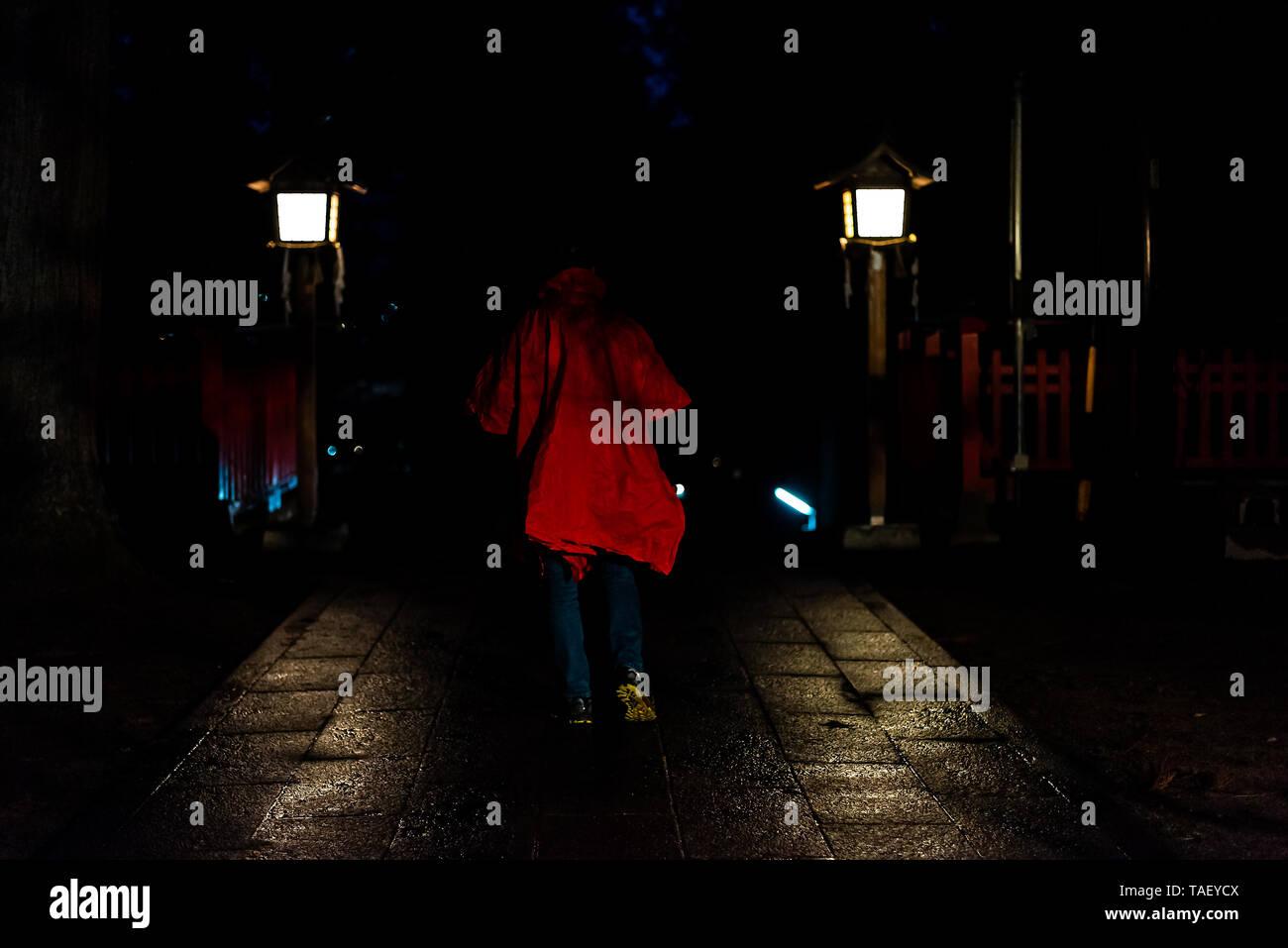 Higashiyama Hakusan Shrine in Takayama, Gifu Prefecture in Japan with man in poncho by entrance to temple building in dark night creepy spooky - Stock Image