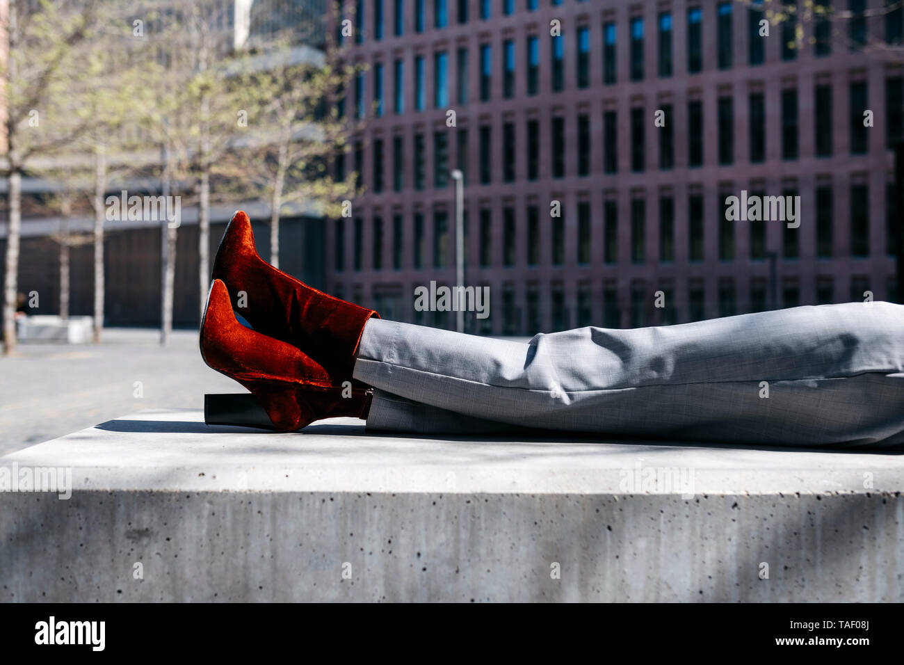 Young businesswoman with red shoes, relaxing on a bench in the city, low section - Stock Image