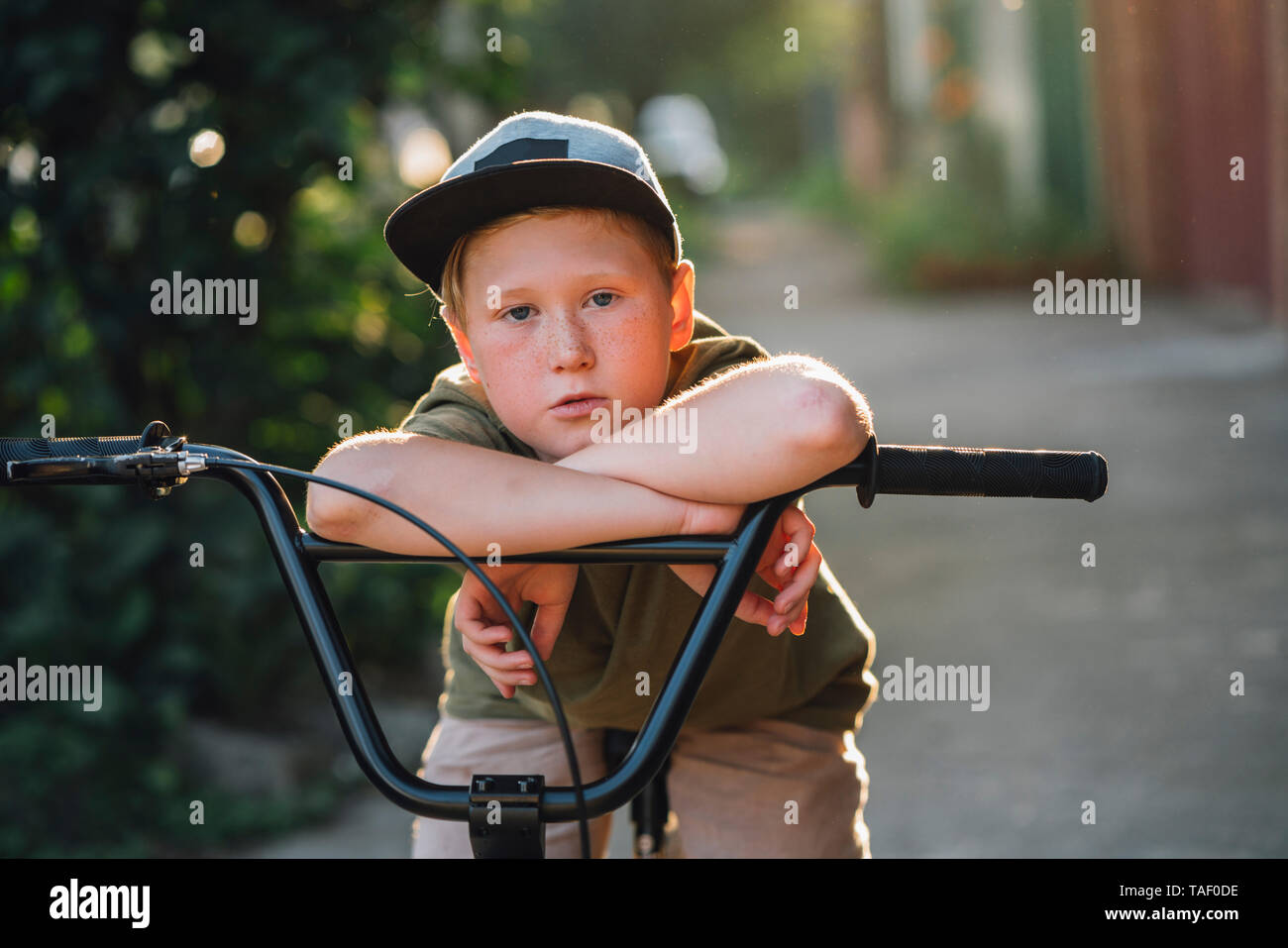 Portrait of boy with bmx bike on road - Stock Image