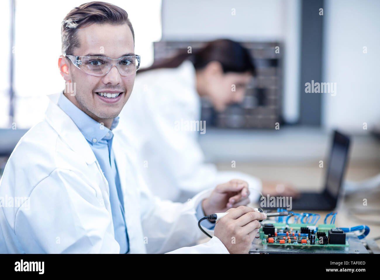 Portrait of smiling technician working on motherboard - Stock Image