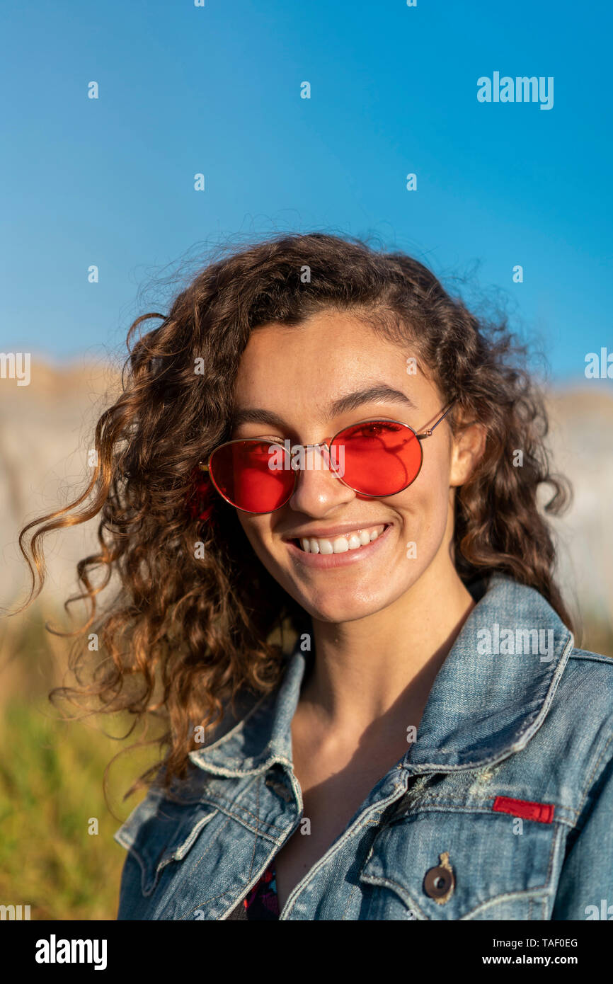 Portrait of happy young woman with curly brown hair wearing red sunglasses - Stock Image