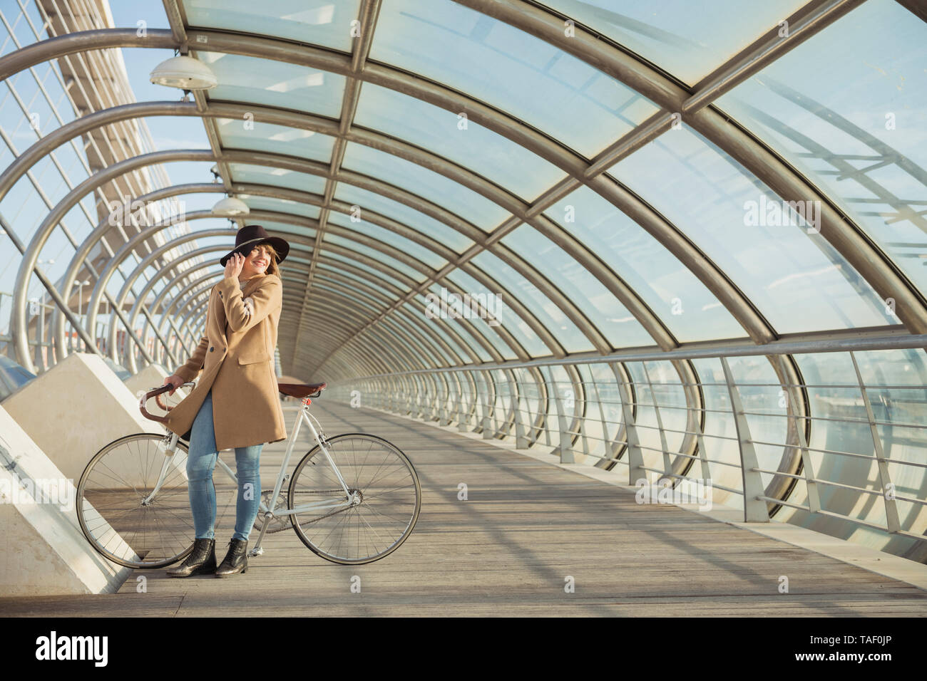 young hipster woman with a bicycle in a modern tunnel - Stock Image
