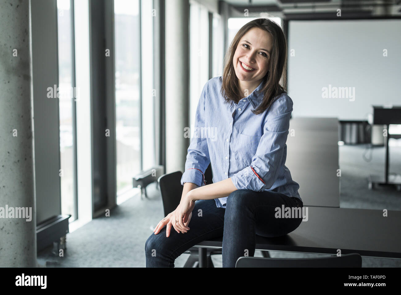 Portrait of smiling businesswoman sitting on conference table in office - Stock Image