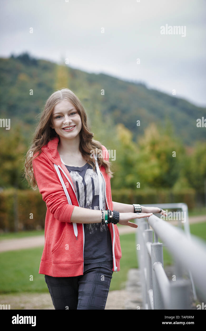 Portrait of smiling teenage girl at a sports field - Stock Image