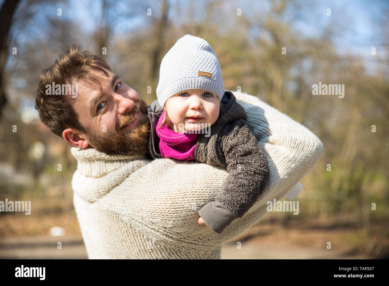 Portrait of happy father carrying daughter in park - Stock Image