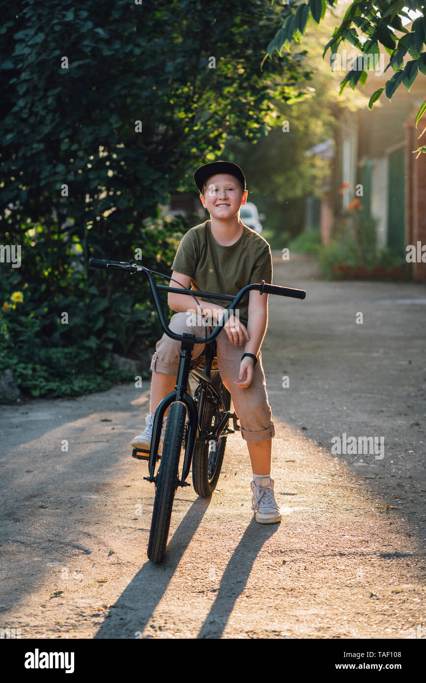 Portrait of smiling boy with bmx bike on road - Stock Image