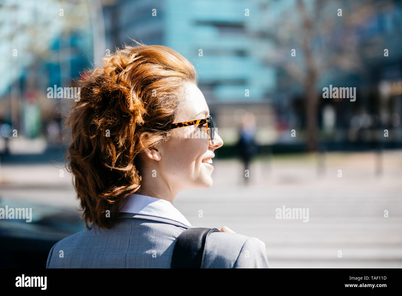 Rear view of a smiling businesswoman wearing sunglasses - Stock Image