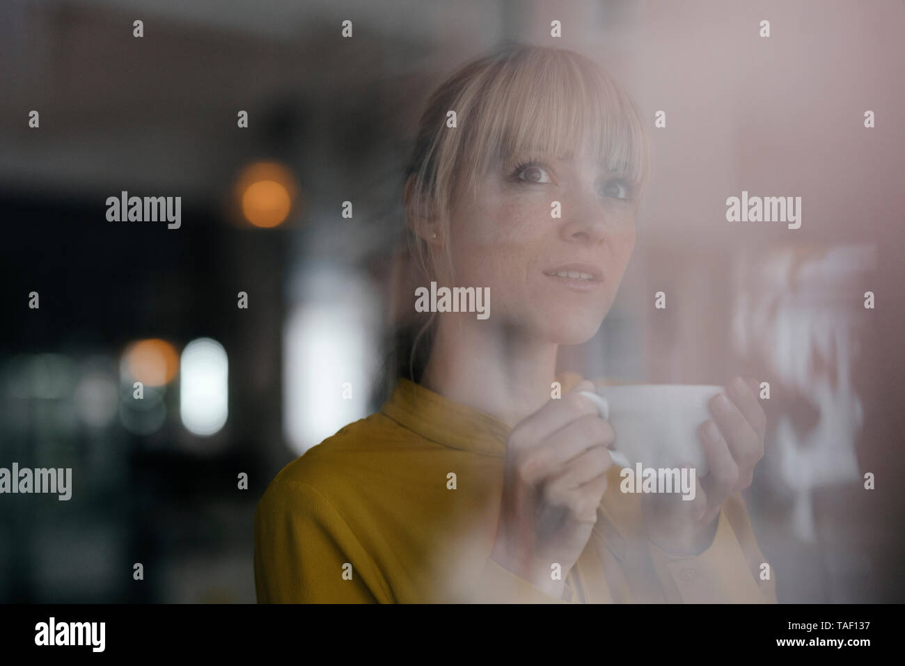 Portrait of a beautiful blond woman standing at window, drinking coffee - Stock Image
