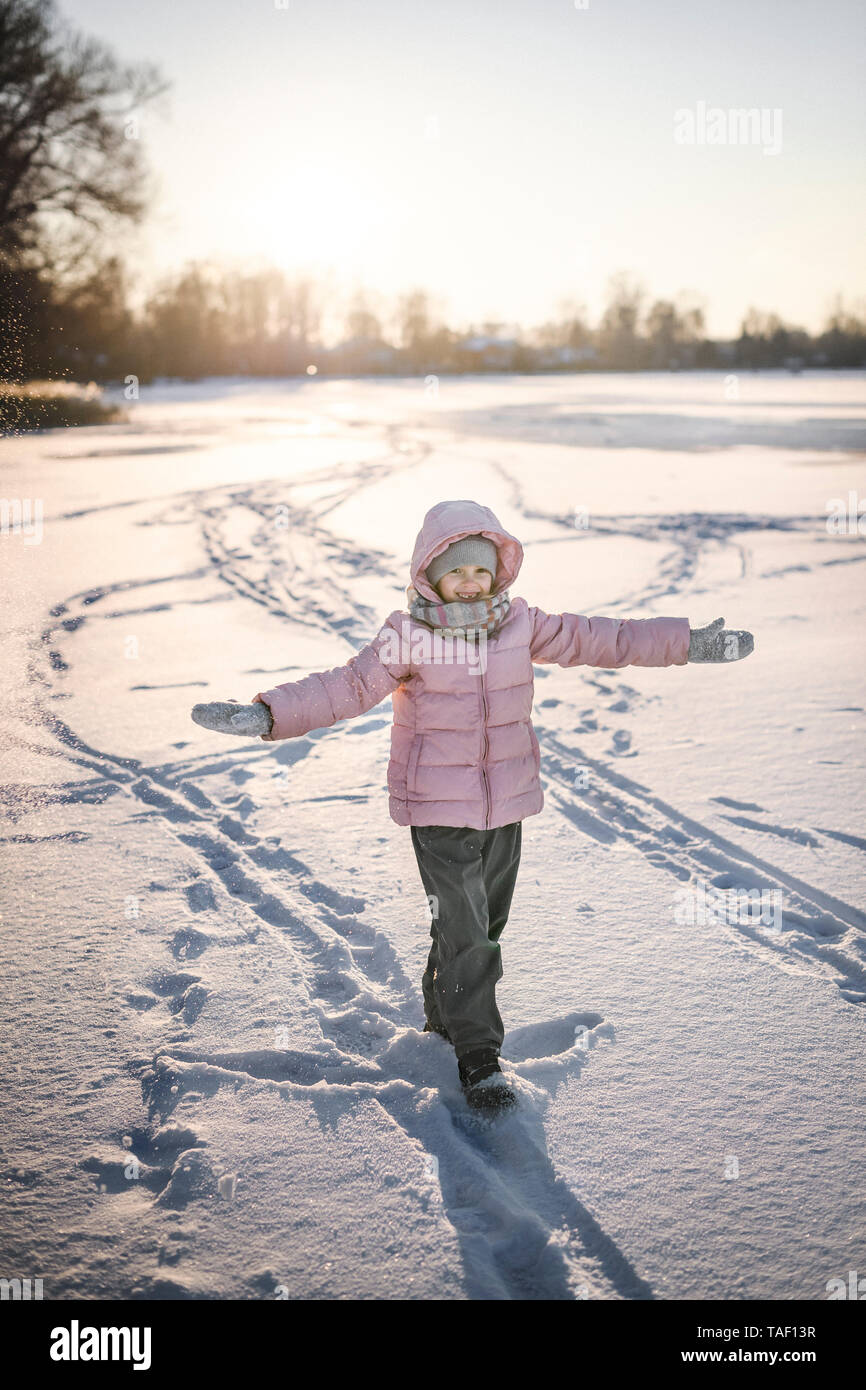 Portrait of little girl standing on snow field - Stock Image