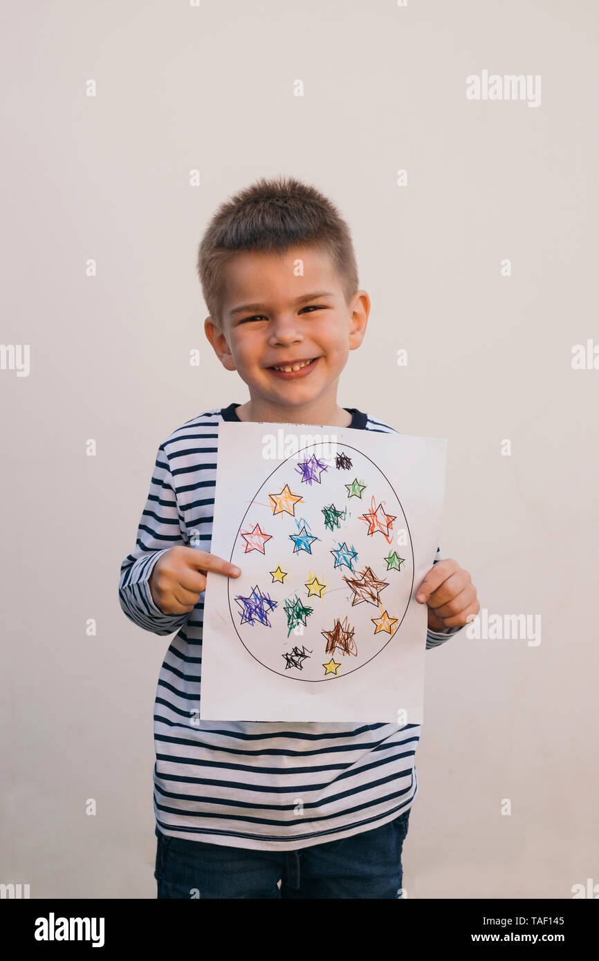 Boy holding his art work and smiling - Stock Image