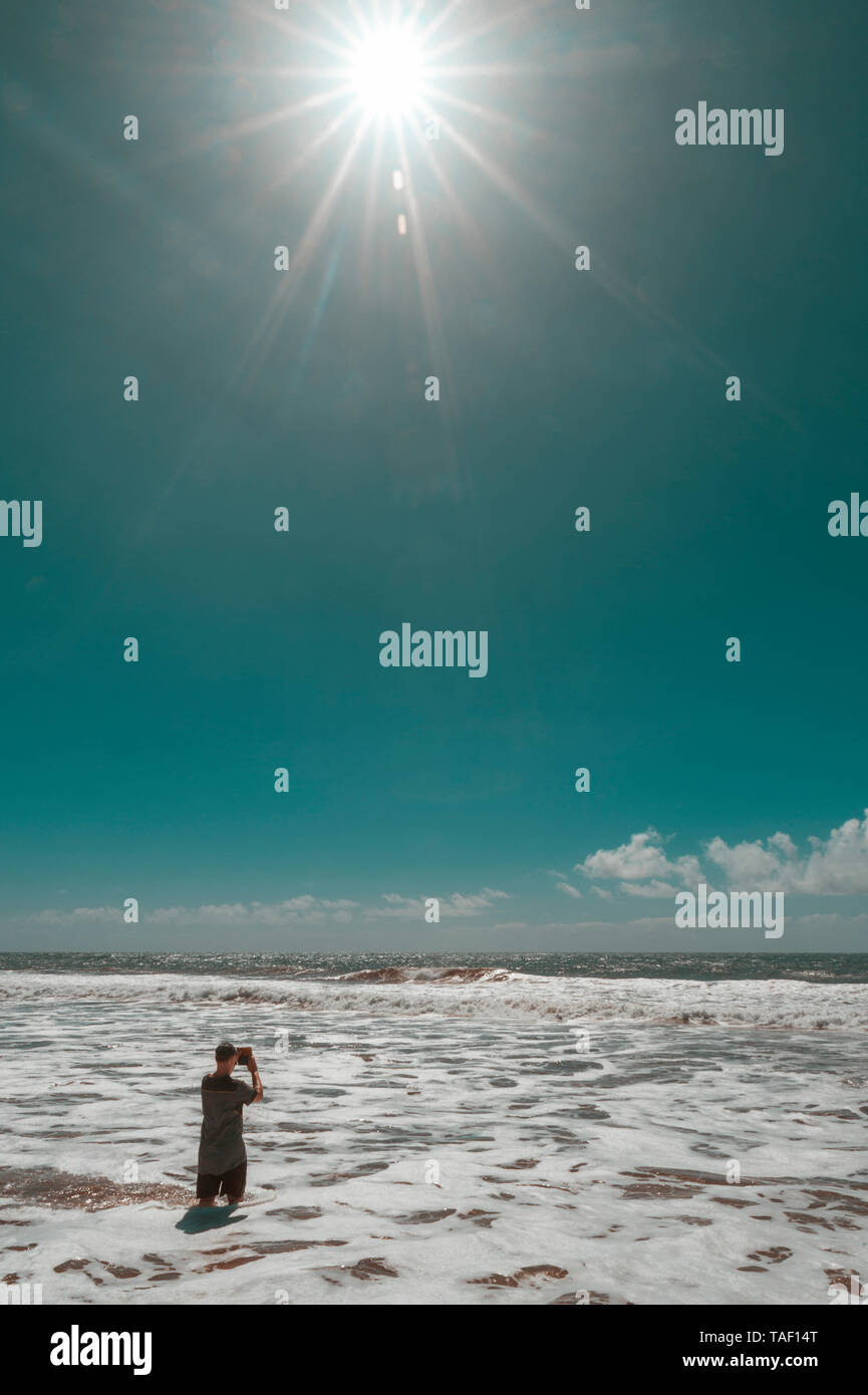 Spain, Canary Islands, Gran Canaria, man standing in water, taking photo with tablet - Stock Image