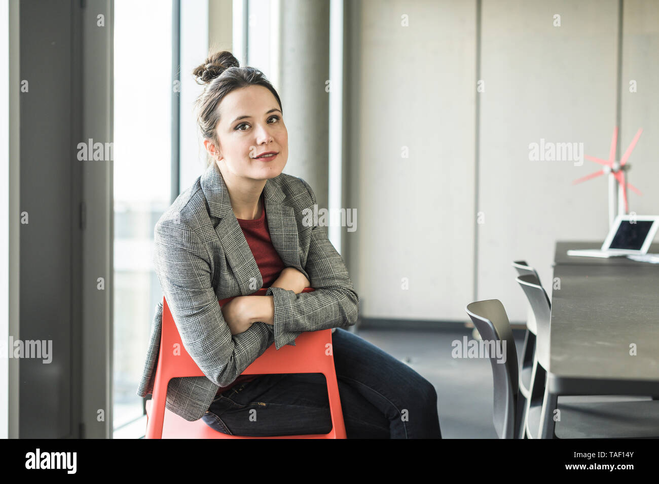 Portrait of smiling businesswoman sitting on chair in office - Stock Image