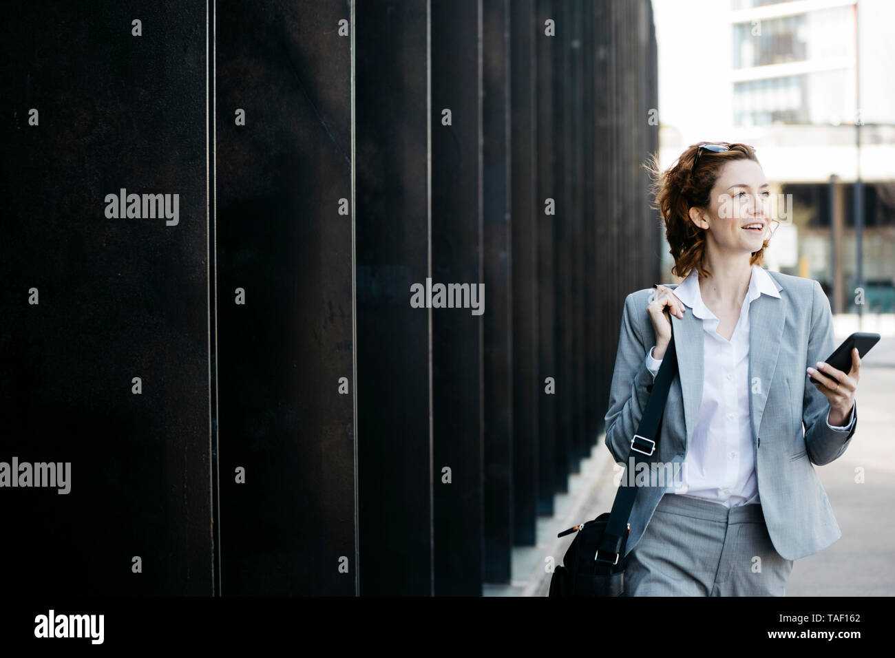 Businesswoman with smartphone, commuting in the city - Stock Image