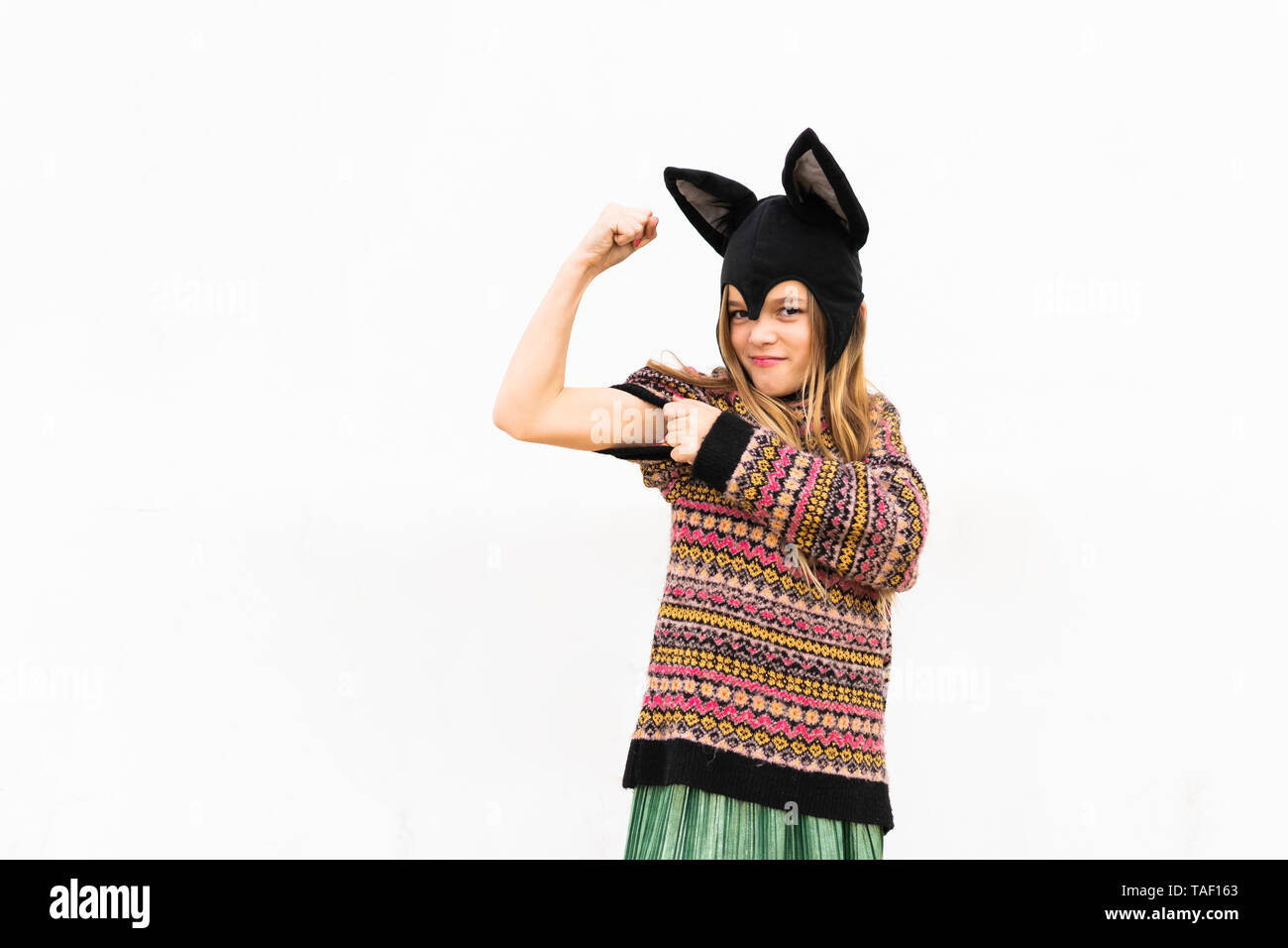 Portrait of girl flexing muscles in bat costume in front of white wall - Stock Image