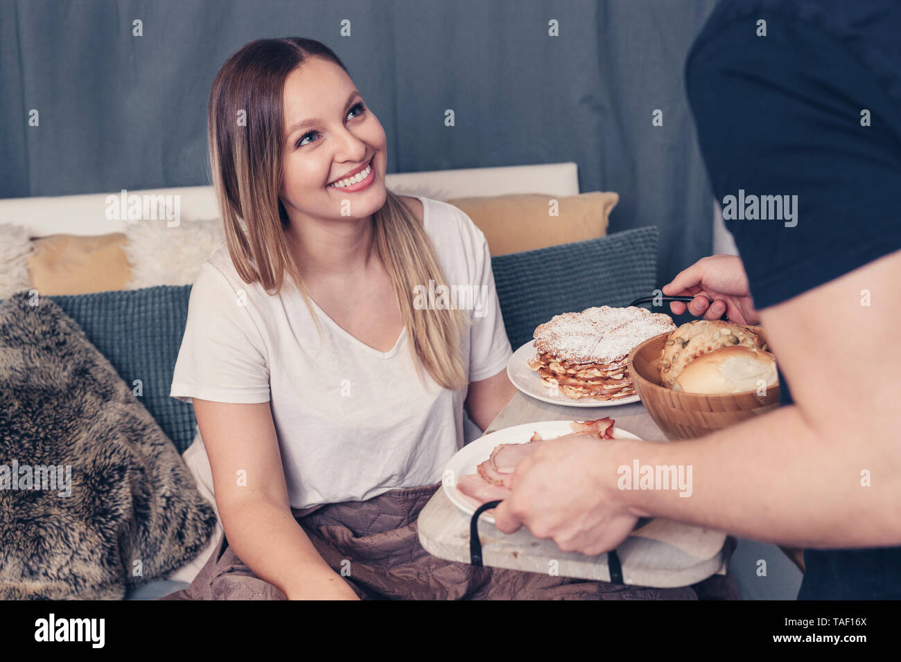 Young man serving breakfast in bed for girlfriend - Stock Image