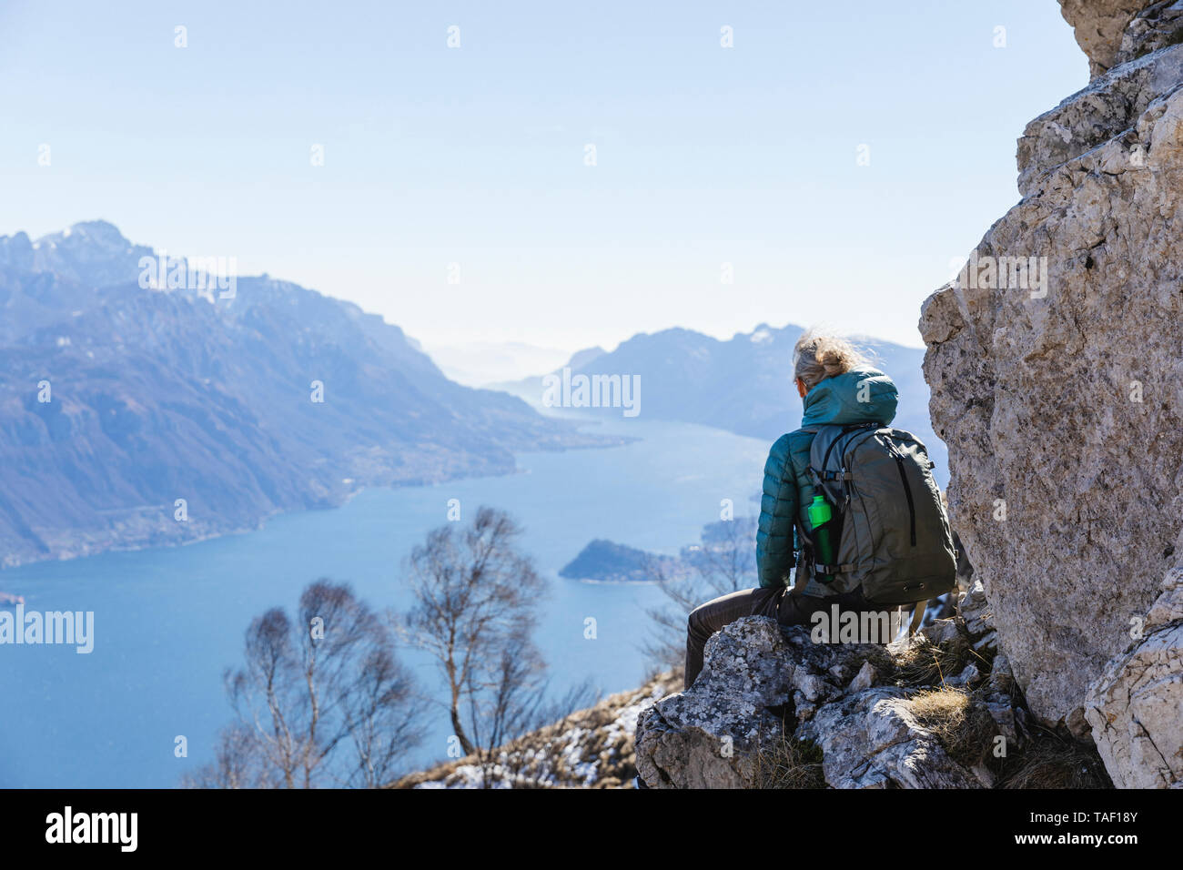 Italy, Como, Lecco, woman on a hiking trip in the mountains above Lake Como sitting on a rock enjoying the view - Stock Image