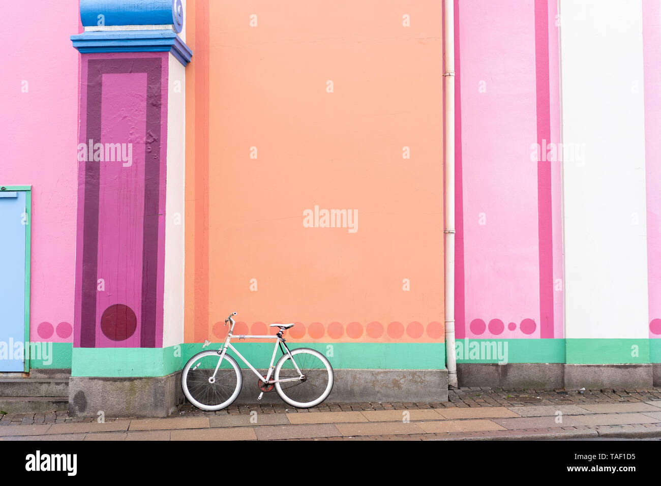 Denmark, Copenhagen, Bicycle leaning on colorful wall - Stock Image