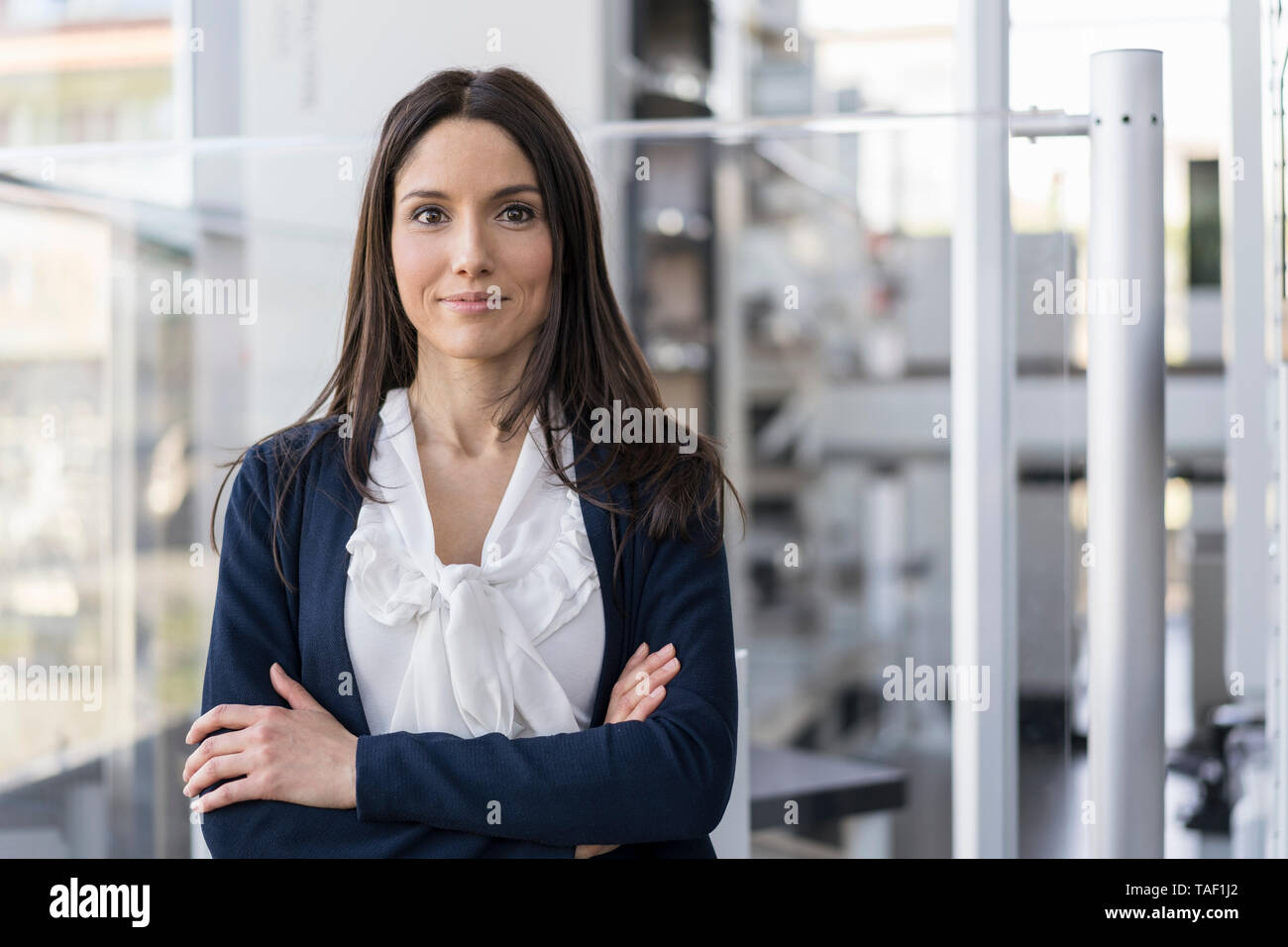 Portrait of smiling businesswoman in a modern factory - Stock Image