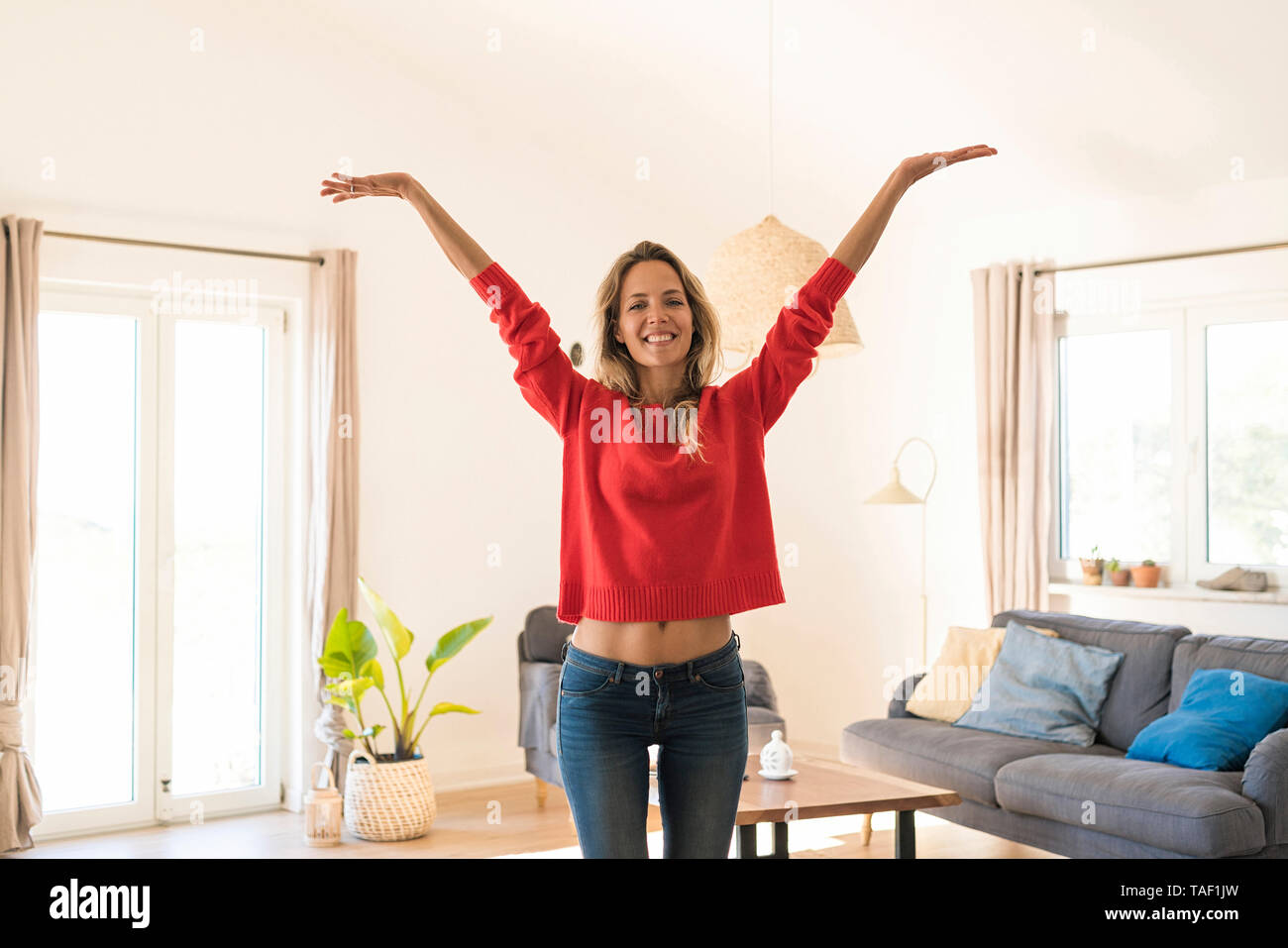 Portrait of carefree woman at home - Stock Image