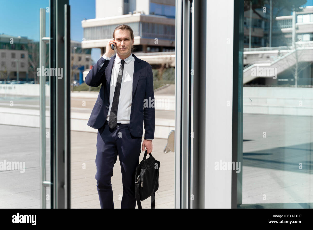 Italy, Florence, young businessman on smartphone outdoor - Stock Image