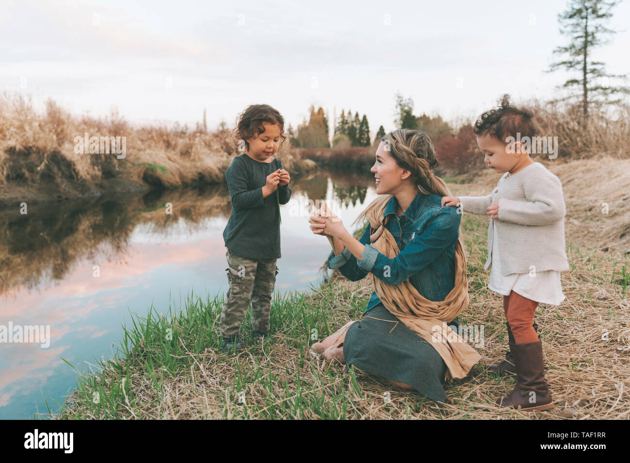 Maother and children playing with a grass blade at a river - Stock Image
