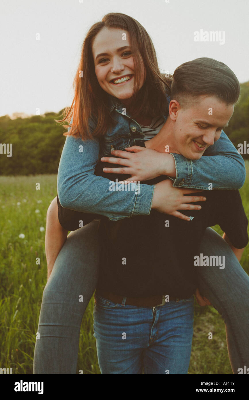 Young man giving his happy girlfriend a piggyback ride in nature - Stock Image
