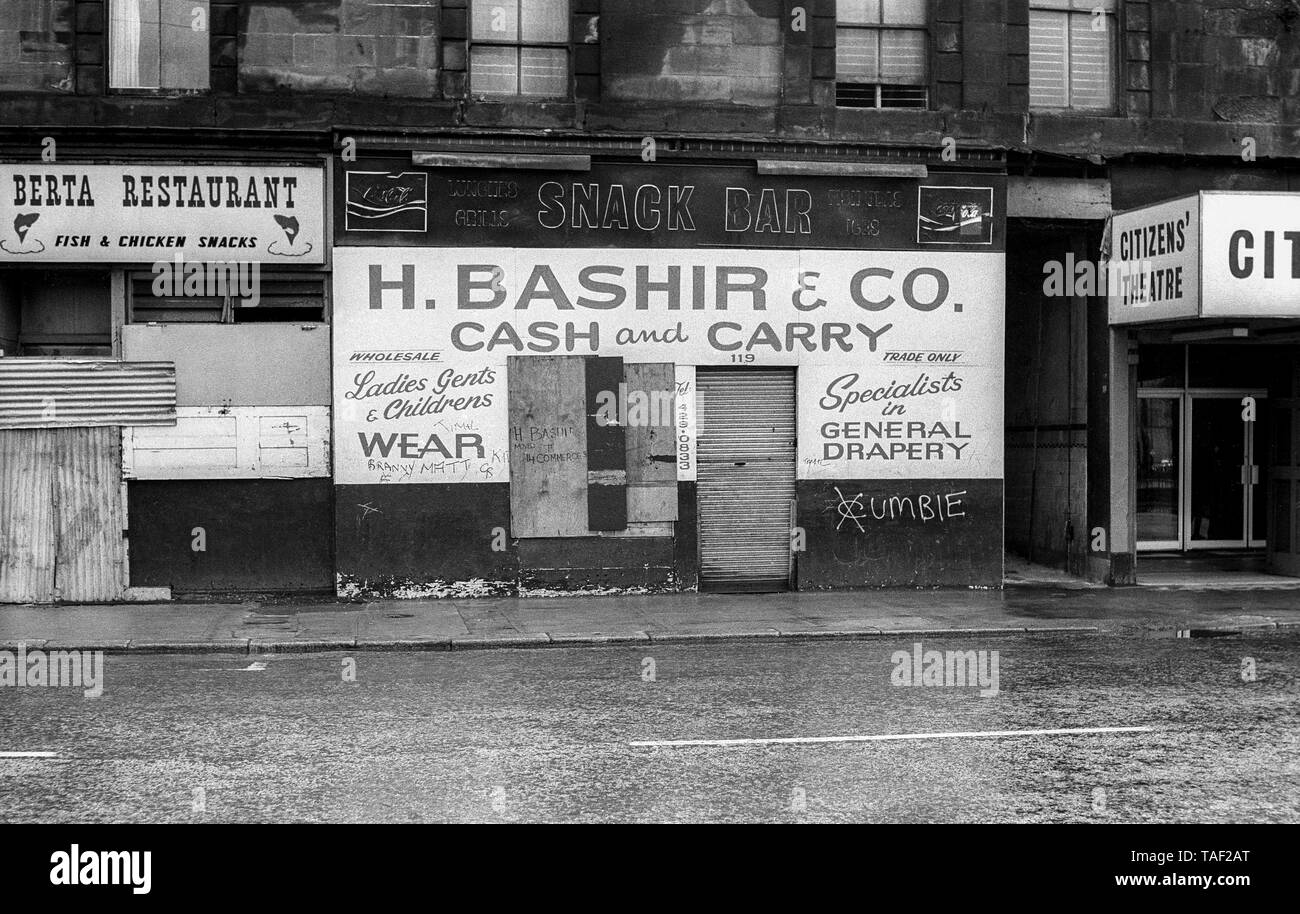 Black & white archive image of closed H Bashir & Co cash and carry shop premises with Cumbie gang sign in Gorbals Street, Glasgow. Cumbie were one of the notorious gangs of the Gorbals area of Glasgow. Photograph taken in March 1977. - Stock Image