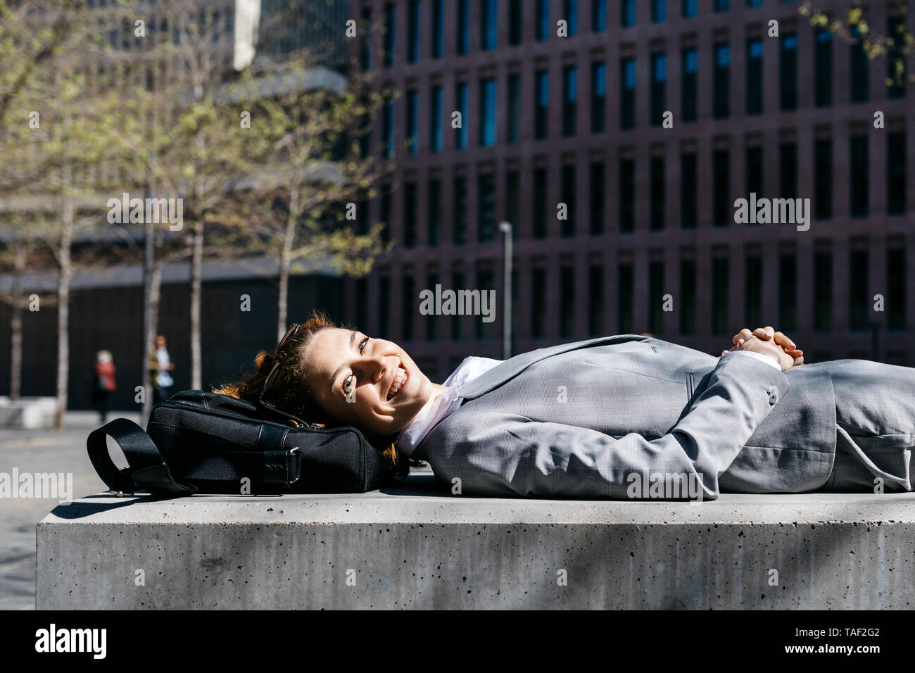 Young businesswoman with red shoes, relaxing on a bench in the city - Stock Image