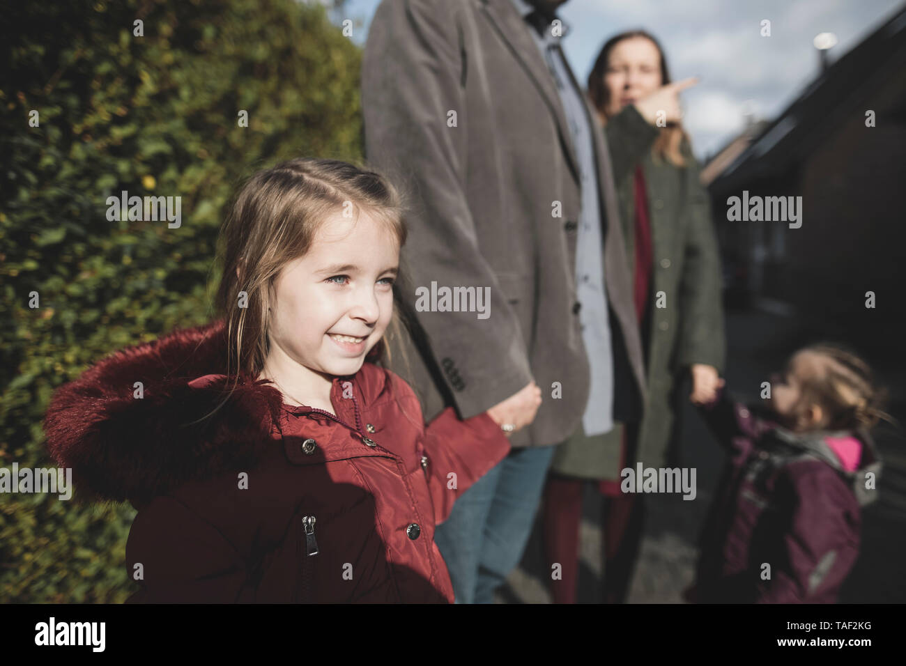 Smiling girl holding hand of her father outdoors - Stock Image