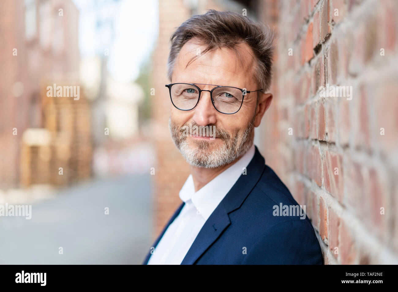 Portrait of confident businessman at brick wall - Stock Image