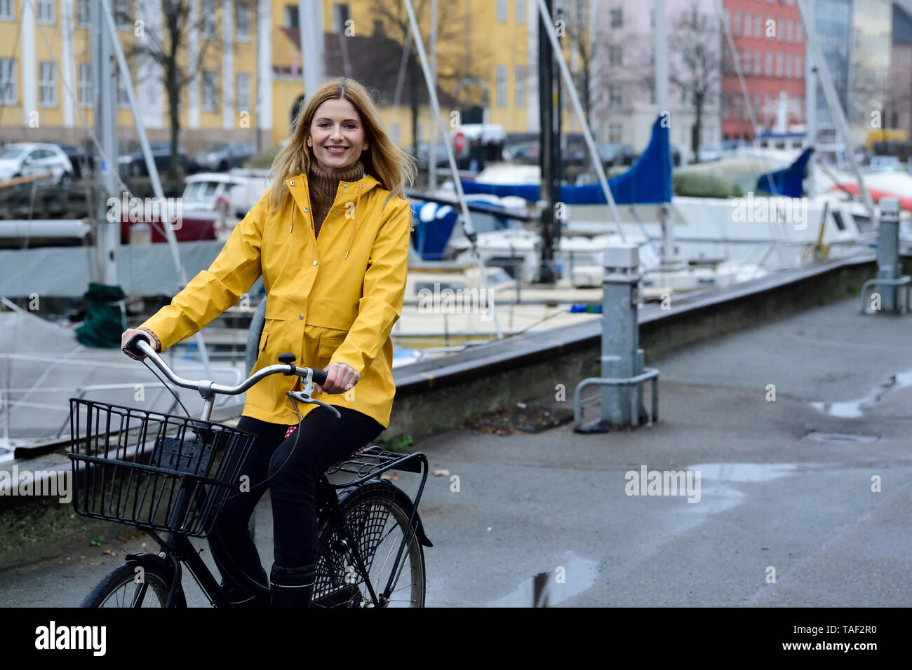 Denmark, Copenhagen, happy woman riding bicycle at city harbour in rainy weather - Stock Image