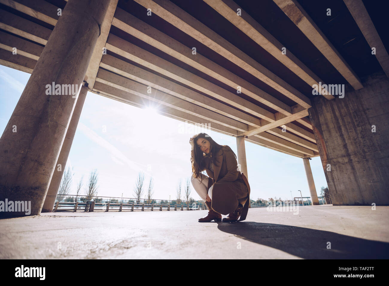 Young woman crouching at an underpass in backlight - Stock Image