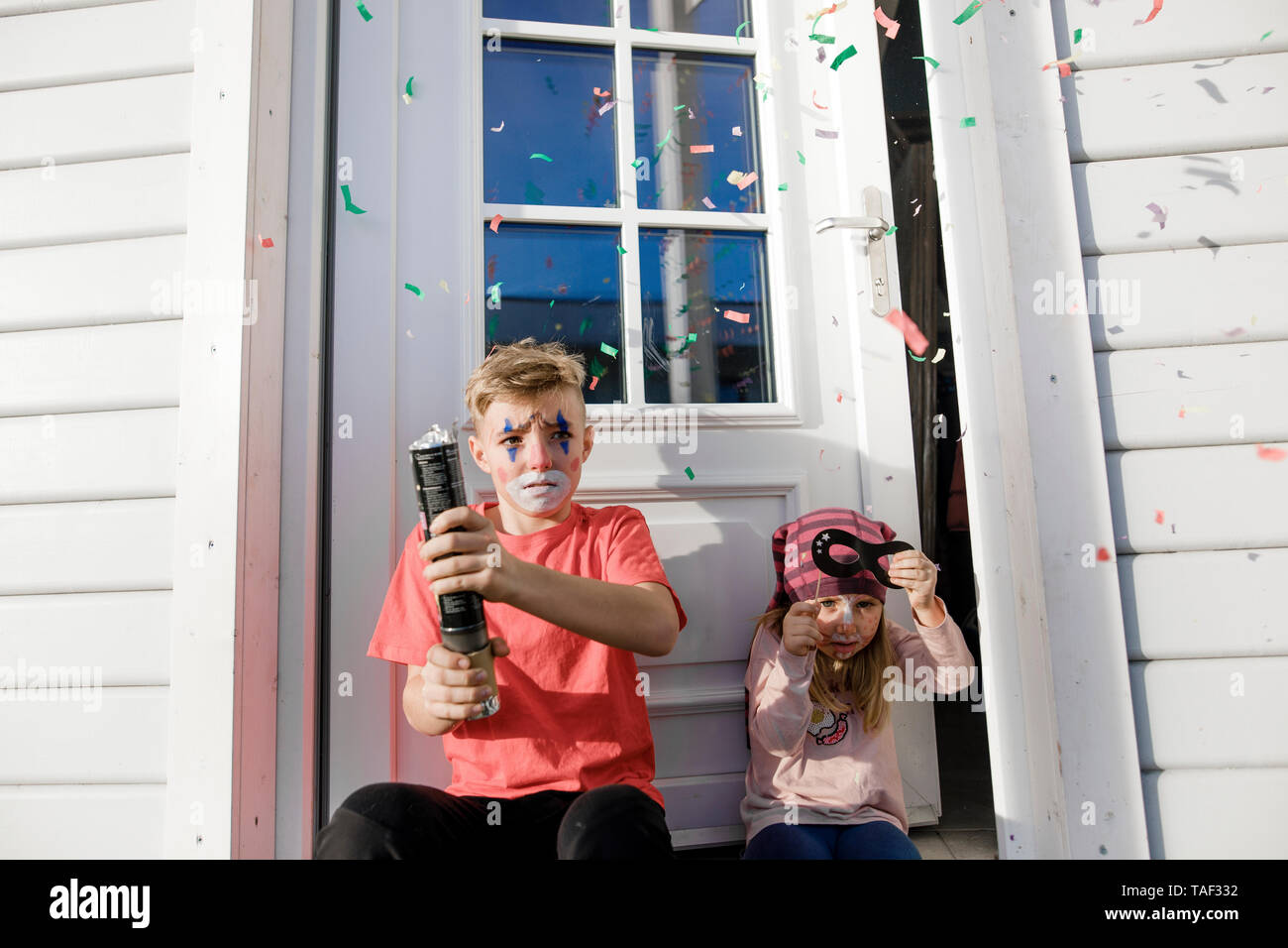 Brother and little sister made up for carnival sitting in front of entry door - Stock Image