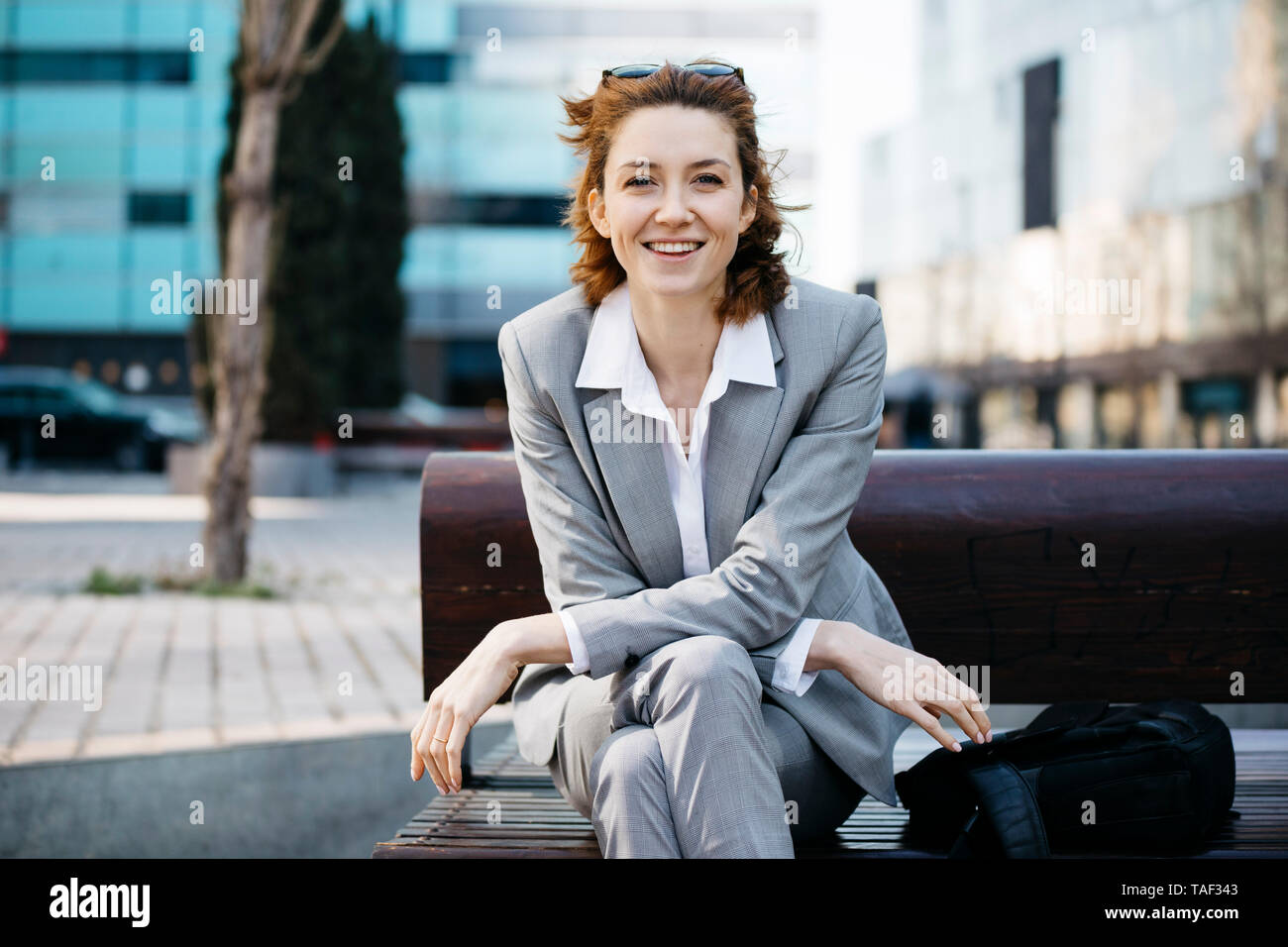 Young confident businesswoman sitting on a bench in the city, looking at camera - Stock Image