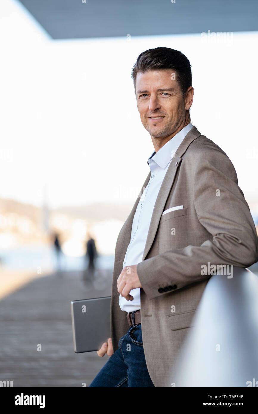 Smiling businessman with tablet standing outdoors - Stock Image