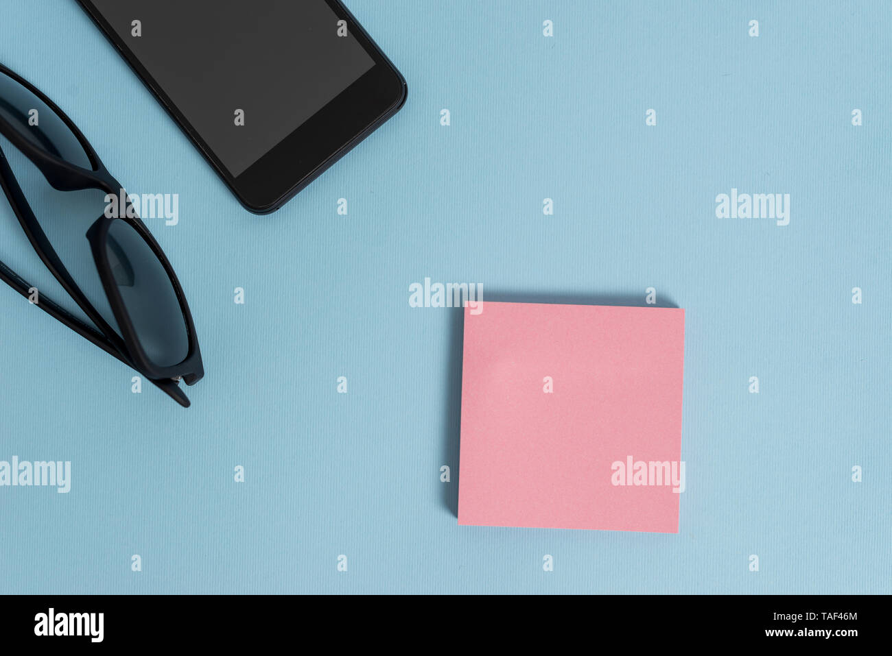 Dark eyeglasses colored sticky note smartphone fashion pastel background - Stock Image