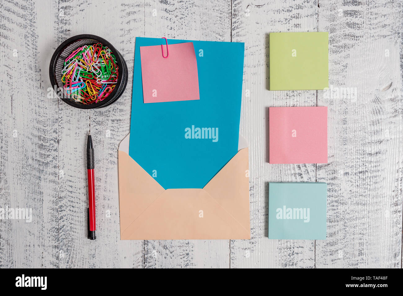 Envelope letter paper sticky note ballpoint clips holder wooden background - Stock Image