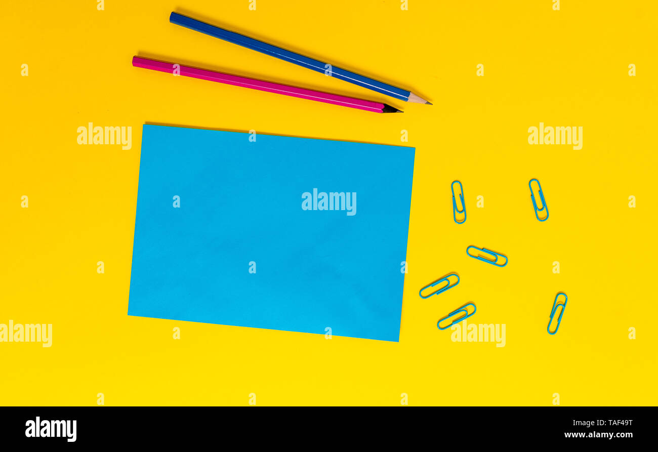 Blank paper sheet message reminder pencils clips colored background - Stock Image